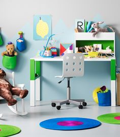 A children's room with a white/green desk that can be adjusted in three…