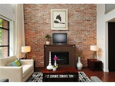 A bricked feature wall highlight the fireplace in a living room. This wall also takes advantage of the natural light to highlight it further.