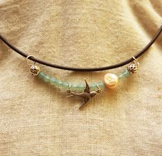 This handmade necklace is inspired by the sky. The necklace features swarovski crystals, a silver bird, and a pearl representative of the moon. The necklace slides on a 16 inch leather cord, and has a tradtional circular clasp. This necklace comes ready for gift giving.