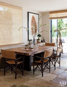 Hallberg and Wiseley designed the dining table; the director's chairs are by Christian Liaigre, the pressed-leaf artwork is by Formations, and the stone flooring is from Exquisite Surfaces.