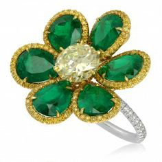 This spectacular ring is quite a statement piece. Six pear shaped emeralds surrounded by fancy intense yellow pave diamond halos form the petals of a floral design.  A 1.47 carat fancy yellow center diamond completes the look and lends additional sparkle that cannot be beat.  0.18 carats of D-F color VS clarity accent diamonds add elegance to the band.