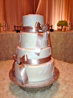 Beautiful white lace flower design covers this 4-tier ivory cake with satin ribbon and broaches.