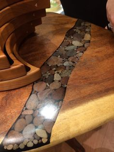 River rock going through table top, router out wood then use rock and pour resin into remaining space