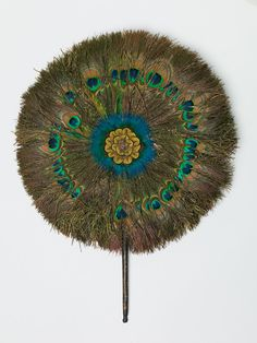 Rigid fan Unknown artist, Indian, India Rigid fan, 19th Century Peacock feathers, mirror, wood stick Height: 50.8 cm (20 inches) Museum Collection 1989.044.8