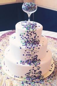 Purple, blue, and teal edible confetti dots spill out of a champagne glass topper. #celebstylewed