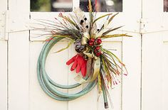 """Fun idea! """"Perfect for the avid gardener or outdoor enthusiast, a garden hose wreath adds character to any doorway. And with the endless possibilities for embellishments, it's easy to switch up the style of your wreath each season."""""""