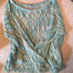 Free people over-the-shoulder boho knit sweater Super cute mermaid knit crochet sweater top in teal aqua and blue with hints of sparkles, by free people. Never worn! It is see through so you'd have to wear a tank top under or wear it as a cover-up to the beach! Could fit any size. Longer in the back Free People Sweaters Crew & Scoop Necks