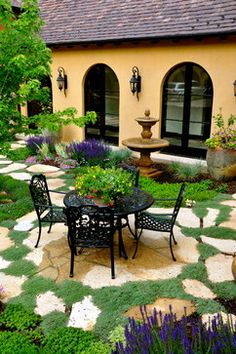 Italian inspired courtyard with slate, moss & purple salvia. Fountain & table makes this .