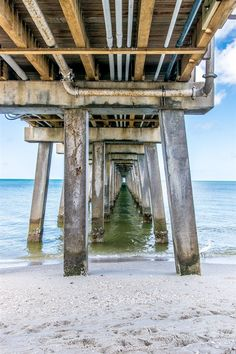 Waves crash under the seemingly infinite columns of the old Naples Pier in Florida.  || #AlexTonettiPhotography #Photography