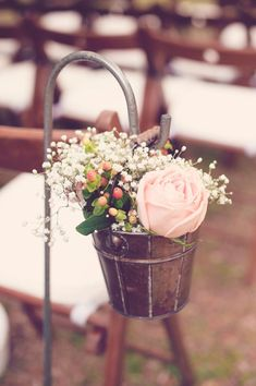 Hang tiny rustic buckets filled with flowers on shepherds hooks to decorate your aisle.  Great idea found on weddingchicks.com