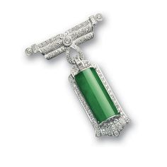 JADEITE AND DIAMOND PENDANT / BROOCH. The pendant suspending a highly translucent emerald green jadeite plaque, set within a diamond-set stylised frame, the surmount decorated with baguette and brilliant-cut diamonds, mounted in 18 karat white gold.