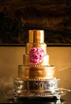 Brides.com: . A four-tiered gold-frosted wedding cake with fresh flower details.
