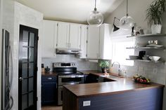 I'm liking the dark butcher block countertops with the navy blue cabinets!