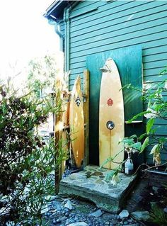 I love the surfboard behind the shower but also the exterior paint color of this house!