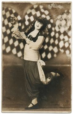 This is a real sepia photo, Avant-Garde postcard of a woman dressed in ethnic clothing posing in front of a harlequin pattern backdrop. She is holding playing cards in her hands. This postcard is in good condition. There is wear on the corners and edges and some places on the upper front that look like damage but they are in the photo itself, perhaps either from developing or simply from age. They are smooth to the touch.
