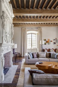 Pierre Yovanovitch juxtaposed low-slung contemporary seating with an exquisitely carved antique fireplace and an exposed-beam ceiling in the living room of