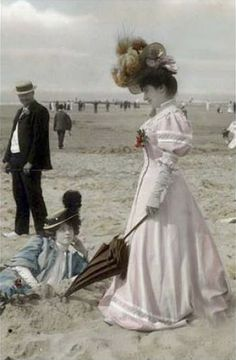 There was a time when going to the beach was a formal affair, complete with extravagant hats, posh umbrellas and very heavy gowns. Tinted postcard. Circa 1890.