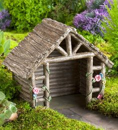 Miniature Fairy Garden Shed: This quaint and detailed fairy garden shed is a durable weather-resistant polyresin structure perfect for your mini garden. Made to look like a wooden garden shed, your fairies will have covered access to their most important tools all year long. Flower detailing adds an enchanting touch, perfect for any well established or beginning fairy village. #fairygarden