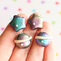 Hi everyone! Here are some kawaii colour shifting star and planet charms! ⭐ These were made using black clay which I dusted with chameleon powder that you can find online. It is designed for nail art, but works great on polymer clay too! It's hard to show just in a photo because it depends on the angle you look at the charm, but one powder shifts from purple to a teal/blue and the other goes from a purple to a yellowy green kind of colour ✨ And yes, one of the planets does have my…