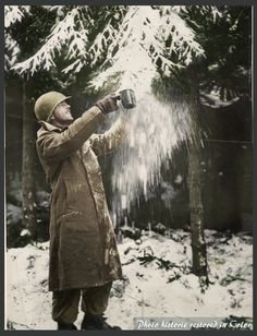 U.S. 101st Airborne Division soldier fills his canteen cup with snow for making coffee in a forest near Foy.