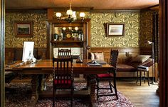 The walls of the dining room on the ground floor are covered in a reproduction of a late 19th-century pattern called Aberdeen Ferns. The antique oak dining table was bought at Housing Works.