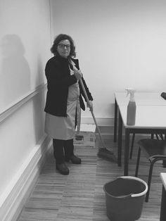 Nesta foto pode-mos ver uma senhora com idade compreendida entre os 45 e 50 anos. Como pode-mos ver é uma empregada de limpeza. Quanto ao cenário em sim pode-mos ver que a senhora segura uma vassoura e que no chão encontrasse um balde e em cima da mesa um género de produto de limpeza. Esta foto foi tirada dentro de uma sala de aula onde esta senhora se encontrava a limpa-la.