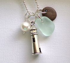 Oregon Coast Beach pebble, natural beach glass next to a sterling silver plated Light House  charm and a tiny 7mm crystal pearl ( reminds me of