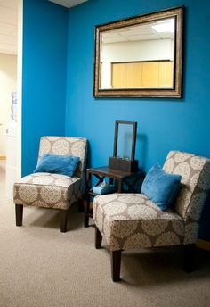 Love the bright blue on one wall with matching pillows and brown chairs!