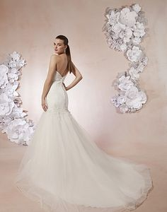Sweetheart / Wedding Gowns / Style #5999 / Available Colours : Ivory/Silver, White/Silver - A sweetheart neckline with a beaded sheer panel on this rushed dropped waist tulle mermaid. The deep V-back neckline with beaded lace appliqués and buttons cover the zipper. This style has a chapel length train (back)