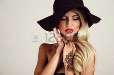 sensuel: portrait en studio de mode de la belle femme sensuelle avec des cheveux blonds avec le maquillage du soir et tatouage au henné sur les mains