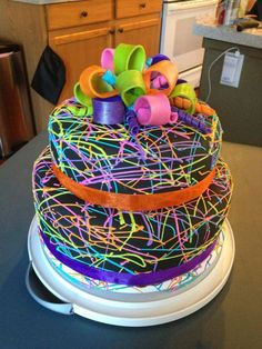 Default - Two tiered black cake with neon splatter paint. I used thinned royal icing dyed neon colors to make the splatter paint. Bow is made from 50/50 gumpaste and fondant. The border is ribbon.