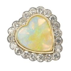 Pretty heart setting for an opal ring! An 18ct gold opal and diamond cluster ring. The pear-shape opal cabochon, within a circular-cut diamond surround. Estimated total diamond weight 2cts