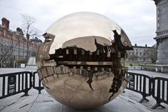 he Sphere Within Sphere, also known as Sfera con Sfera, is a series of sculptures created by Italian sculptor Arnaldo Pomodoro depicting an enormous metal sphere with a cracked surface revealing an intricate interior with another cracked sphere inside. Pomodoro originally created it for the Vatican Church in the 1960s, but later began building them for other organizations and can now be found in prime locations all over the world