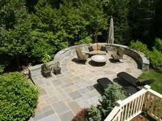 We carved out a sunny stone patio using flagstone and fieldstone on this wooded slope in a McLean backyard