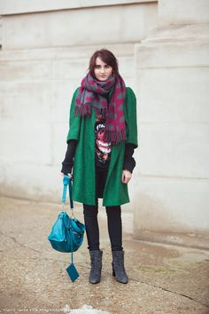 Anouk in a green coat, polka dot scarf, BALENCIAGA rottweiler sweater, black skinny jeans, gray suede boots, and teal BALENCIAGA purse.