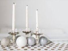 Dressed-Up Champagne Flutes : For a glitzy centerpiece (think New Year's Eve), plastic champagne flutes are the perfect-size vessels to hold taper candles. Add a touch of glamour with inexpensive metallic confetti or ornament shards you can find at most craft stores. Dress up the table with your favorite ornaments and a patterned table runner made from a long strip of gift wrap you might have on hand.