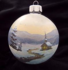 Hand painted Christmas ornament of a church and a stream in the snow.