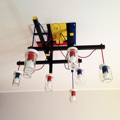 Laura has created a ceiling lamp inspired by the art of Mondrian and the architecture of Rietveld: it consists of a wooden structure painted with enamel paint, a tin can used as a ceiling rose, old Nutella jars and red and blue electrical wires. An original idea and with an eye for recycling, we love it! Italy:www.creative-cables.it USA: www.creative-cables.com Europe&Australia: www.creative-cables.net #homedecor #home #ideas #design #lighting #recycling #nutella