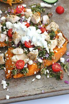 Greek Loaded Sweet Potatoes: Sweet potatoes, garlic hummus, red onion, cherry tomatoes, feta, chicken, tabbouleh and tzatziki sauce! // The Baker Mama