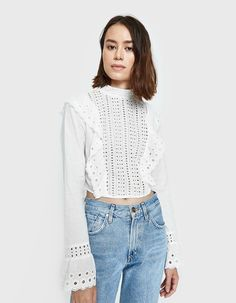 Long sleeve top from Farrow in White. Sheer fabric. Eyelet lace details throughout. Band collar. Back zip closure. Cascading ruffles down front and back bodice. Long sleeves with flounce cuffs. Straight hem. Fitted.  • Cotton Voile • 100% cotton • Han