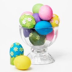 Vibrant Dyed Eggs with Flowers ~ To get bright and colorful eggs, coat them multiple times using an egg-dye kit. Once they're mostly dry, roll them in glitter. Let dry completely. Finish with pretty floral stickers to create a simple and festive Easter decoration.