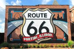 The Route 66 shield is one of our oldest murals. It is located on the back of the Route 66 Association of Illinois' Hall of Fame & Museum. There is a drive-up paved with bricks from the original Route 66, and guests can drive their cars up in front of the mural for photographs. This painted shield is the largest Route 66 shield in the world, and has been featured in many ads and magazine stories.