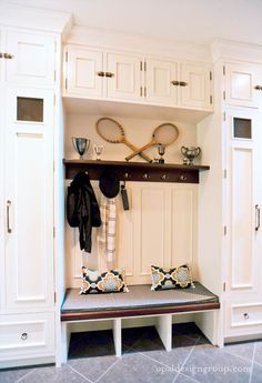 Great mudroom.  Love the mix of white and dark wood.  Also love the vintage sports items.