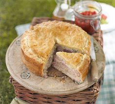 Picnic Pie butter , for greasing 2 x 500g blocks puff pastry 350g sausagemeat or skinned sausages (pork & apple variety works well) 2 apples , peeled, cored and grated 2 onions , grated 2 tbsp thyme leaves 16 thick slices cooked ham , fat trimmed from edge 4 tbsp Dijon mustard 2 eggs , beaten to glaze