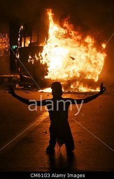 Oct. 12, 2012 - Cairo, Egypt - A protester kneels before a burning bus near Tahrir Square after a day of clashes between supporters of the Muslim Brotherhood and several opposition political parties. The two destroyed buses had been used to bring Muslim Brotherhood supporters to the square to protest against the opposition parties.© ZUMA Press, Inc. / Alamy