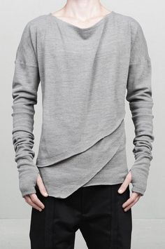 A salient asymmetric oversized knit top crafted from a fine wooland cashmere blend. It's nuance is a mixture somewhere betweenthe unyielding force of neutral grey and the warm earthly power ofthe beige color. The oversized silhouette features an elongateddrop shoulder sleeves with thumb holes. Several layered piecesform a diagonal structure creating this asymmetric proportions leftwith raw edges. At the rear part is located a leather graphicrepresentation - abbreviation of the concept…