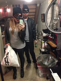 DIY Ban Robbers Couple Costumes. (Black and white striped shirts, black pants, black eye mask, black beanies, and stuffed pillow cases with money signs)