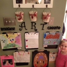 """An at home  """"kids art gallery"""" to display all of the kiddos great work! The girls & I got plain unfinished wood letters from Michael's, black spray paint & plain clip boards from office depot...after that-all you need to do is spray paint & use a hammer & nails! Now you have a cute, stylish way to show off all of that art they proudly bring home from school...we are so excited about our new home art wall! Side note...you can paint the clip boards & letters in any color & use any buckets to…"""