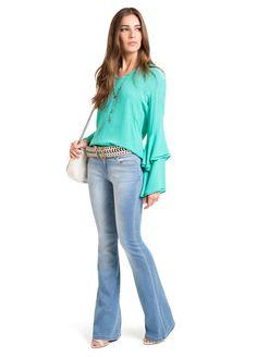 Calça jeans com lavagem mais clara e modelo flare. É um  must have no armário, que combina com tudo. A sugestão é usar com camisas leves e delicadas. A composição é 66,5% algodão,