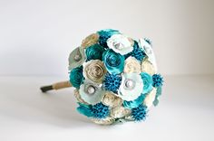 Bridal bouquet made from books with roses, poppies, sweetgum, in teal and ivory.